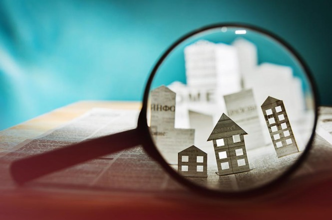 Paper house under a magnifying lens